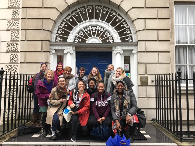 The Georgetown group poses in front of the blue door of the Royal College of Midwives in London.