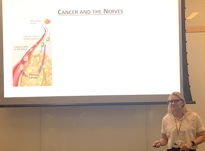 """Human science senior Sara Misiukiewicz (NHS'20) delivering an oral presentation in front of a projection screen with an image and the title, """"Cancer and the Nerves."""""""