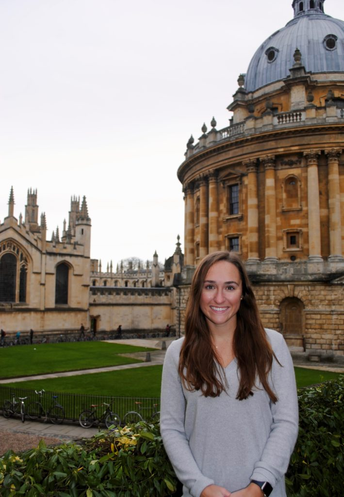 Anna Schildmeyer stands in front of the University of Oxford buildings in England.