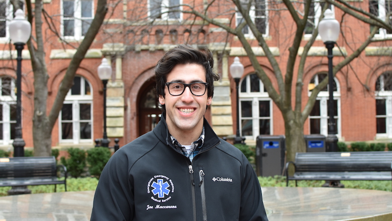 Joseph Maccarone, in his jacket from the Georgetown Emergency Response Medical Service, stands in Dahlgren Quadrangle and poses in front of Healy Hall.