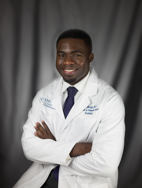 Dr. Philip Oladeji poses in a physician's clinical coat in a formal portrait.