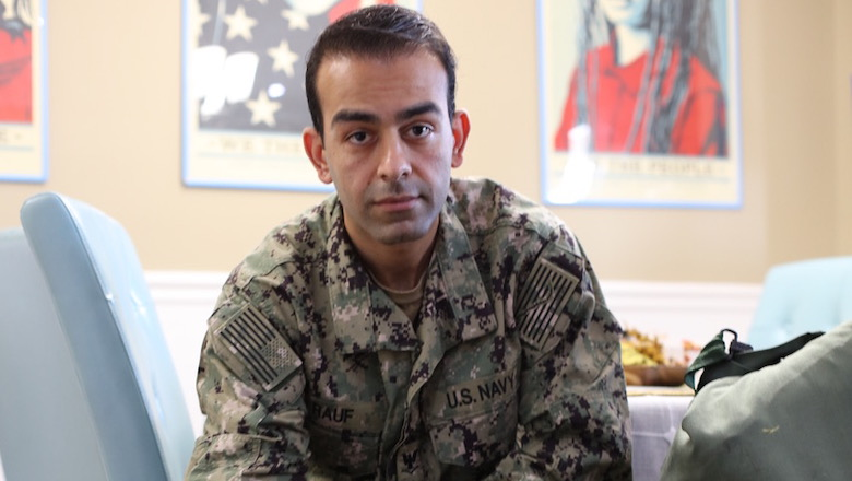 Safiullah Rauf (NHS'21) in his U.S. Navy Uniform seated before a dining room table and portraits on the wall.