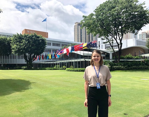 Emily Graul (NHS'20) stands on a lawn in front of the flags of various countries near a World Health Organization building.