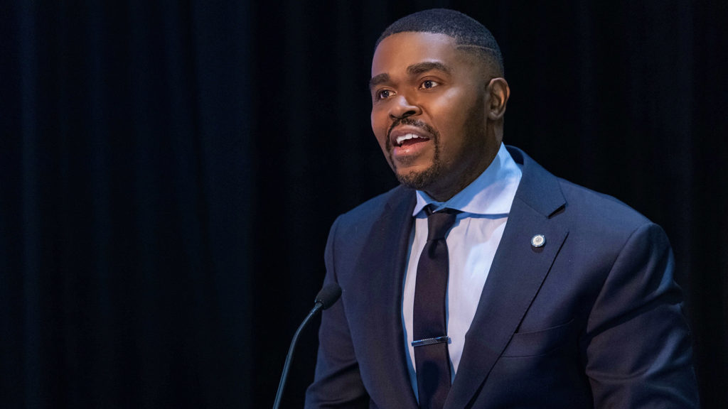 Dr. Christopher King speaks at a podium during an event on campus.