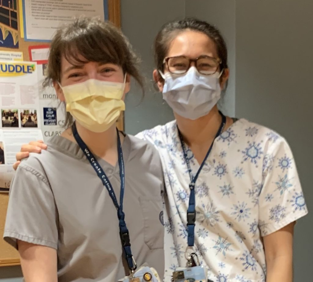 Moira Redmond (NHS'17) and Catherine Zolbrod Freeman (NHS'17) stand in clinical attire and masks