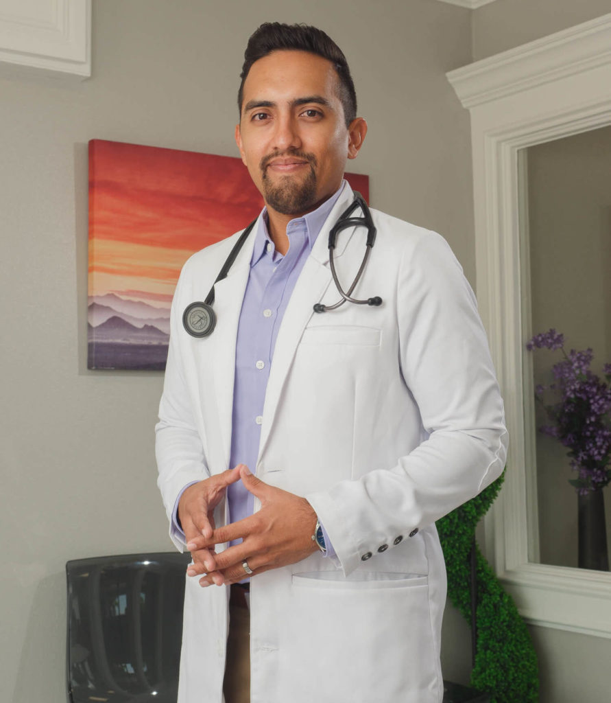 Michael Menchaca, in a white coat and stethoscope, stands in his clinic.