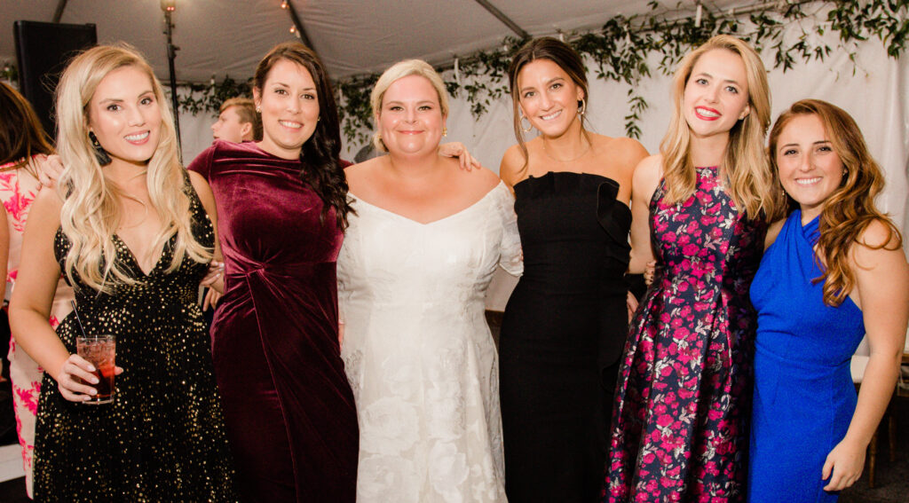 A photo at a wedding with five attendees posing with the bride.