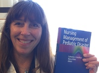 Catherine Joy Manz Goodhue poses holding a copy of her new textbook, Nursing Management of Pediatric Disaster.
