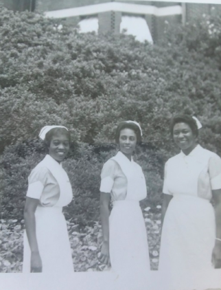 Dr. Bernardine Lacey (center) stands in an early 1960s photo in a nursing uniform with classmates at the Gilfoy School of Nursing.