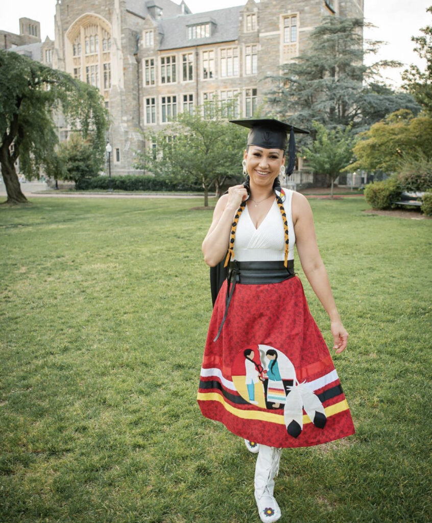 "Nordica Owens stands in front of White-Gravenor Hall on Georgetown's campus wearing her graduation cap and a special ribbon skirt she had made to help connect ""western medicine with traditional medicine."""