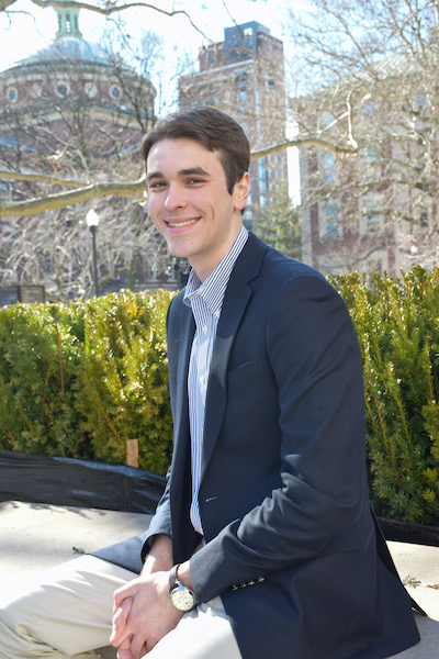 Matthew Chakwin (NHS'21), wearing business attire, sits down in front of plants and buildings.