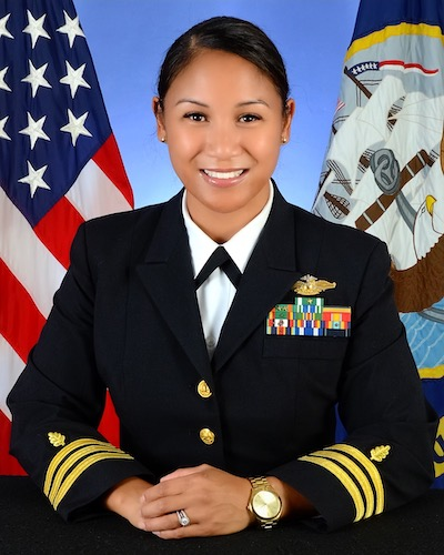 Commander Hannah C. Starnes (NHS'05) in her naval uniform in front of the United States flag and the United States Navy flag