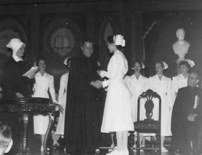 Nursing students on stage at a ceremony in Gaston Hall with priests and a sister