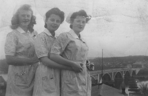 In November 1942, three nursing classmates, in uniform, pose together, likely on the rooftop of the old hospital complex, with the Key Bridge behind them.