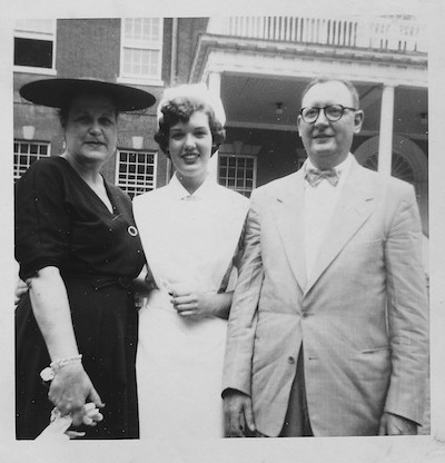 A nursing student, in the mid-1950s, stands with her parents near Old North on Georgetown's campus in her nursing uniform