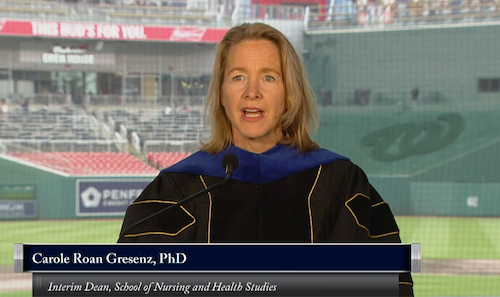 A screen shot of Dr. Carole Roan Gresenz speaking at the Georgetown Commencement with Nationals Park seats behind her.