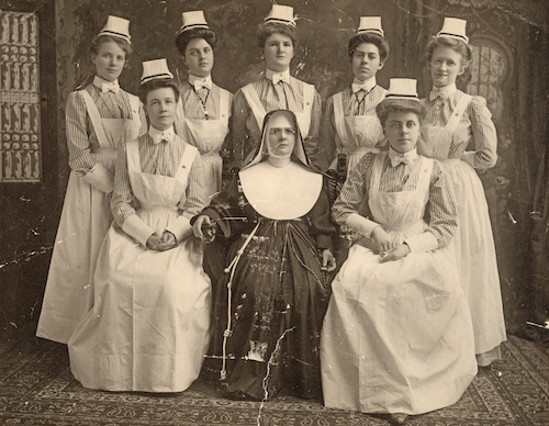 An image of a graduating class of nurses from Georgetown in the early 20th century wearing their nursing uniforms and posing with a religious sister who led the school.