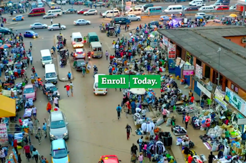"""A photograph of a city street with cars and an urban market with the words """"Enroll Today."""""""