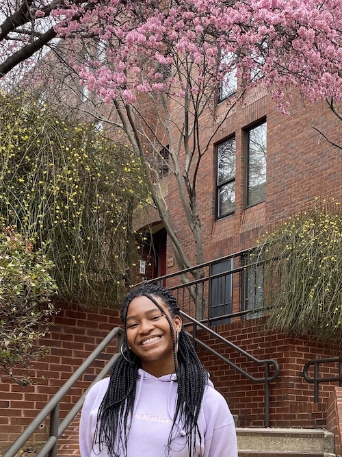 Melody Emenyonu stands on Georgetown's campus in front of a residence hall and trees in blossom.