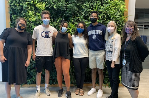 A group of students and professors stand in front of an interior wall with greenery growing on it.